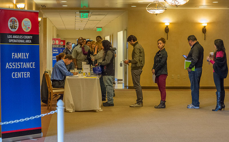 People in line checking in at a family information center